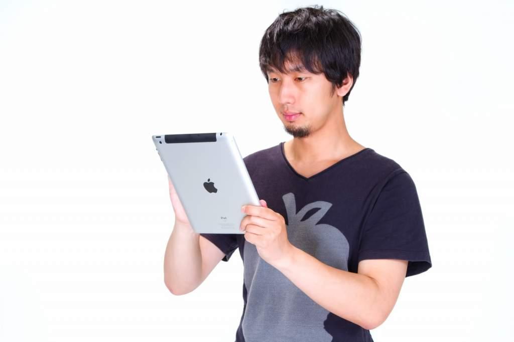 iPad をいじる男性