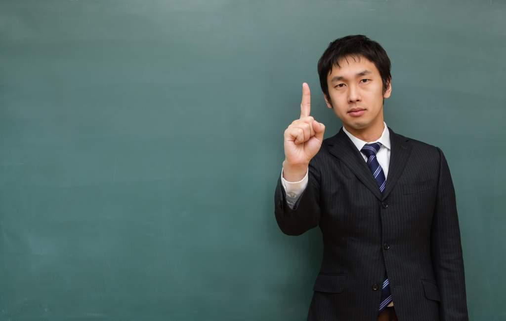 「目指せナンバー1」をする塾の講師 [モデル:大川竜弥]