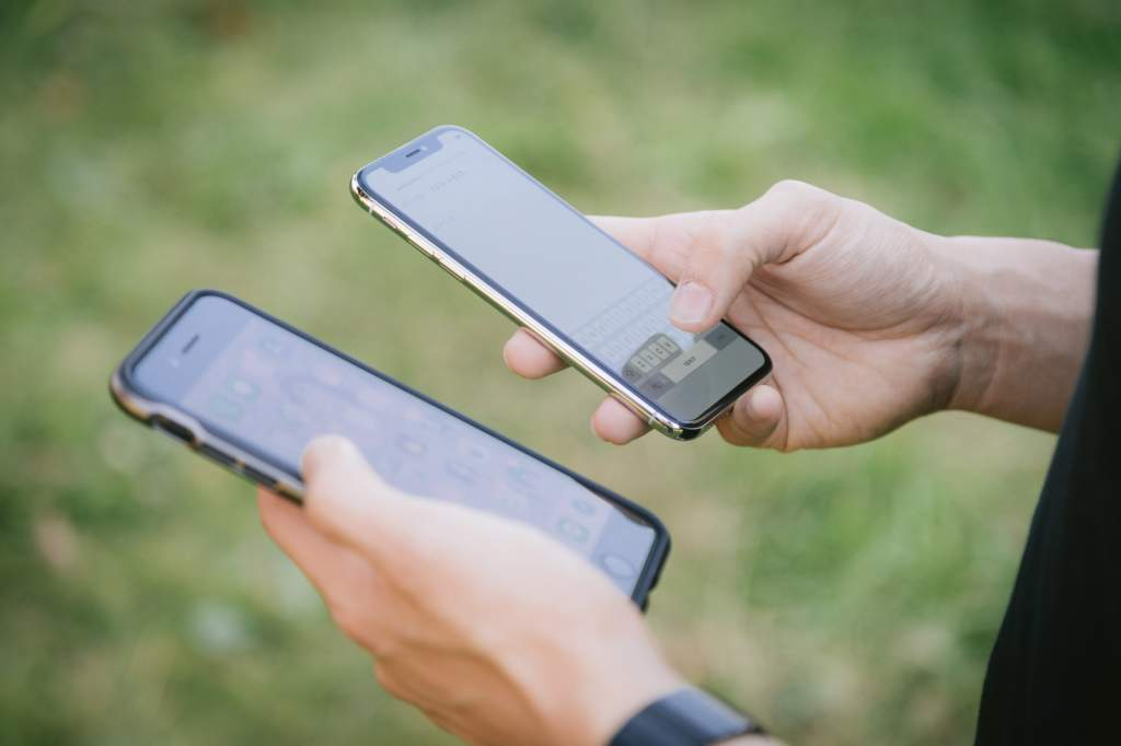 2台のスマホ(iPhone)を操作する男性の手