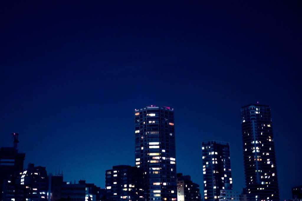 部屋の明かりがまばらな高層マンション