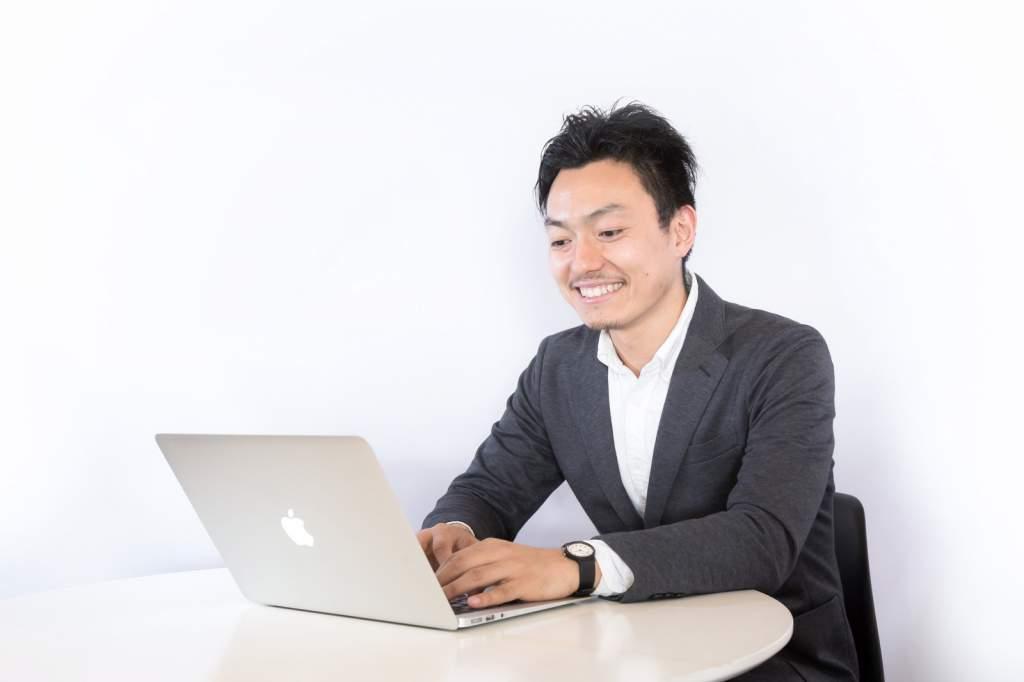 笑顔でパソコンを扱う男性