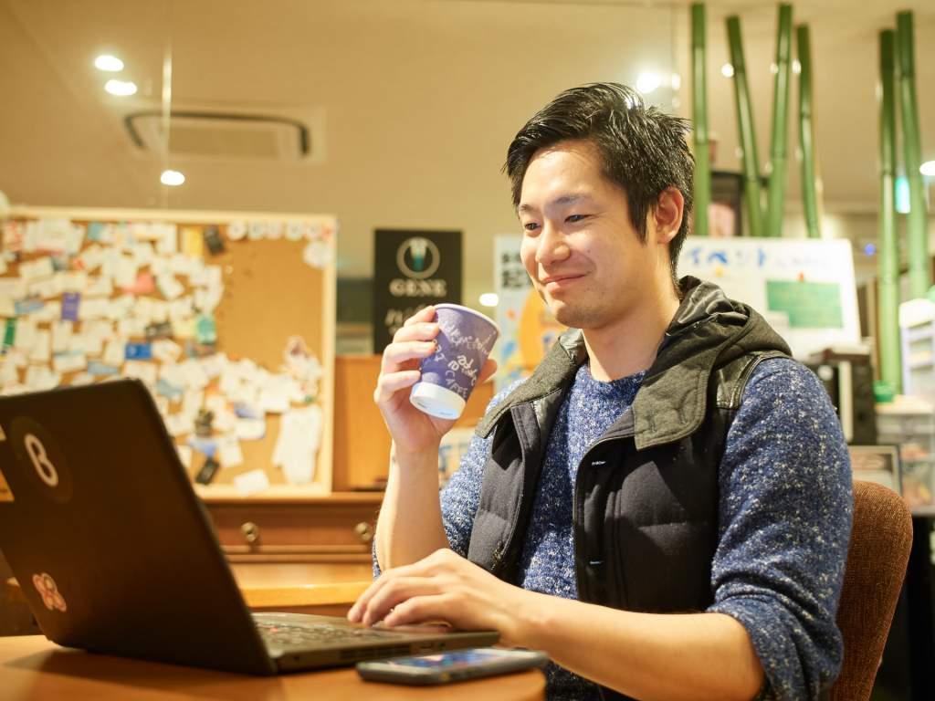 パソコンを見ながら微笑む男性