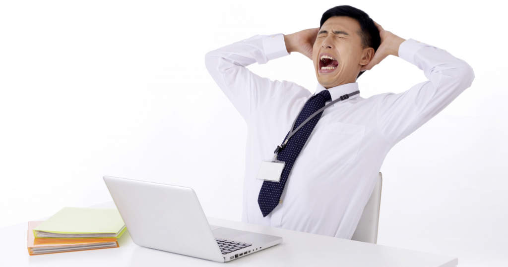 パソコンの前でイライラする男性