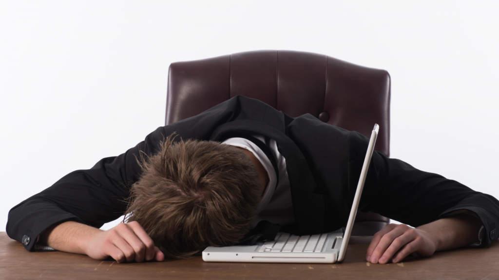パソコンの上で眠る男性