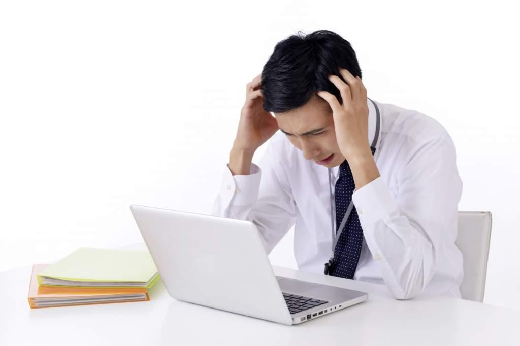 パソコンの前で頭を抱えて困るビジネスマン