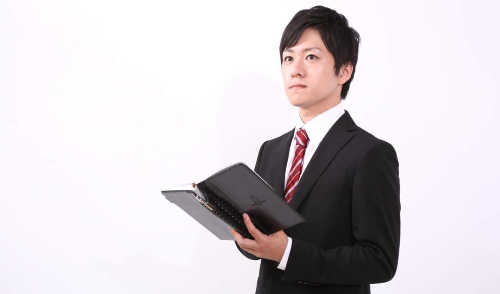 手帳を手に取り考えるビジネスマン