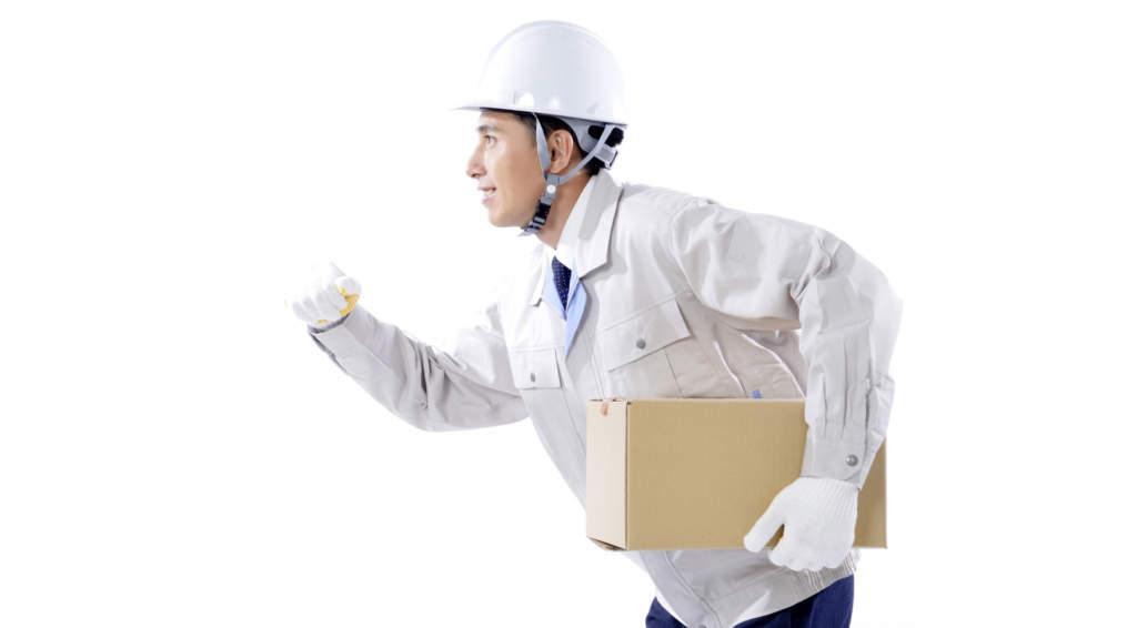 段ボール箱を抱えて走る工事作業員