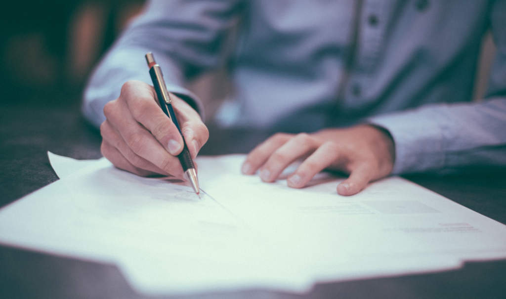 紙に文字を書く男性