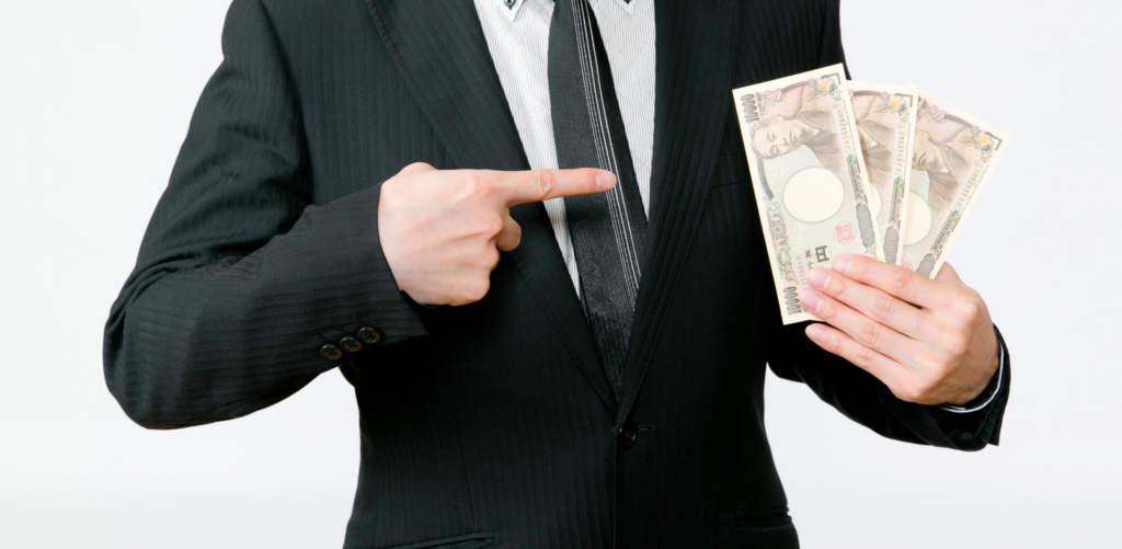 お金を指さすビジネスマン