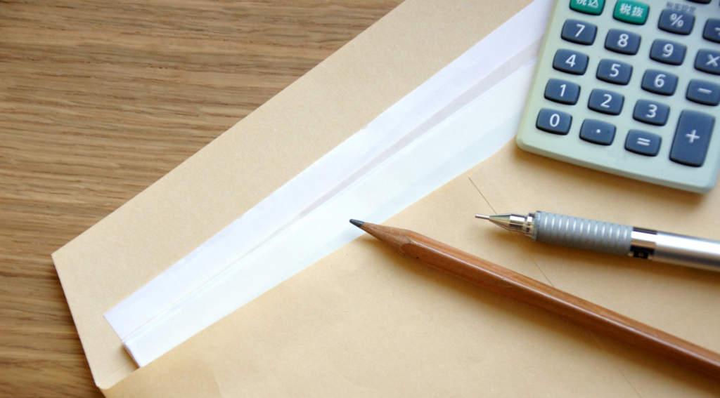 封筒に入った書類・ペン・電卓