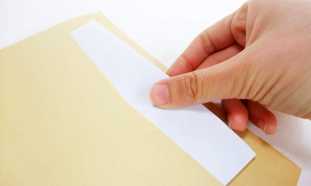 封筒から書類を出す
