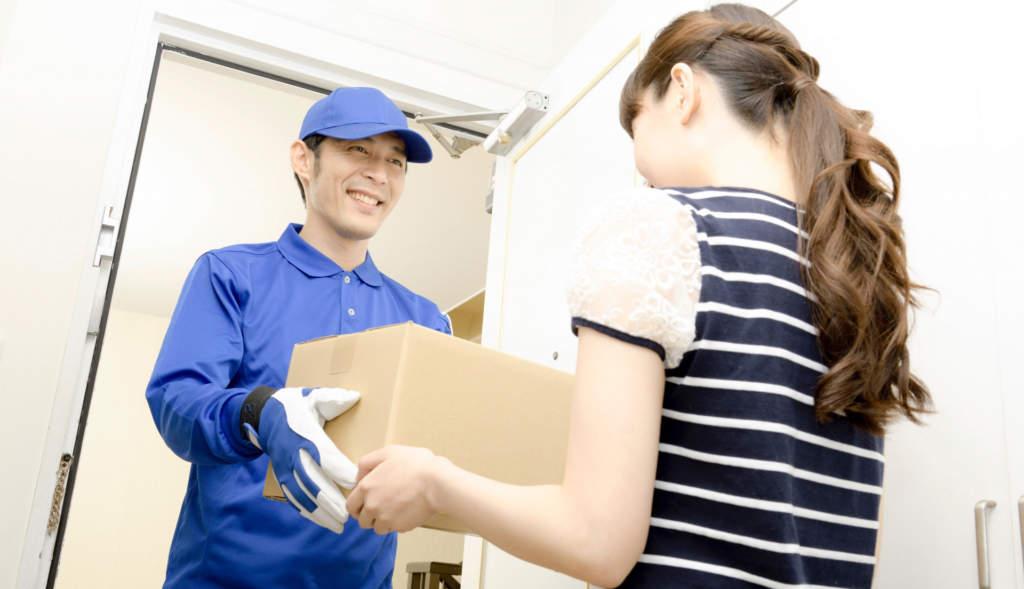 宅配業者に荷物を渡す