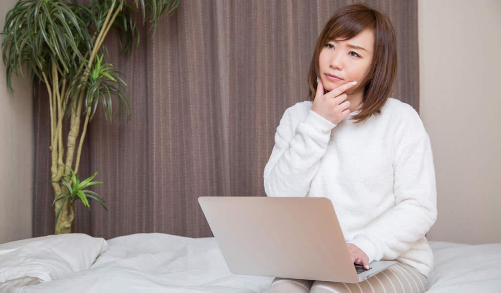 ノートパソコンを見ながら考えごとをする女性