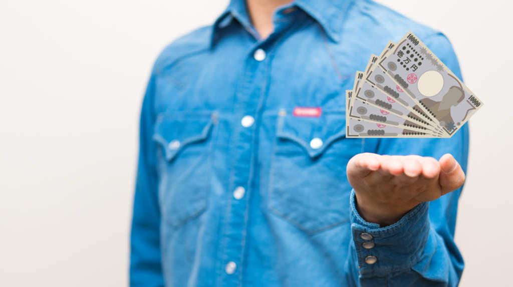 お金を手の上にのせる男性