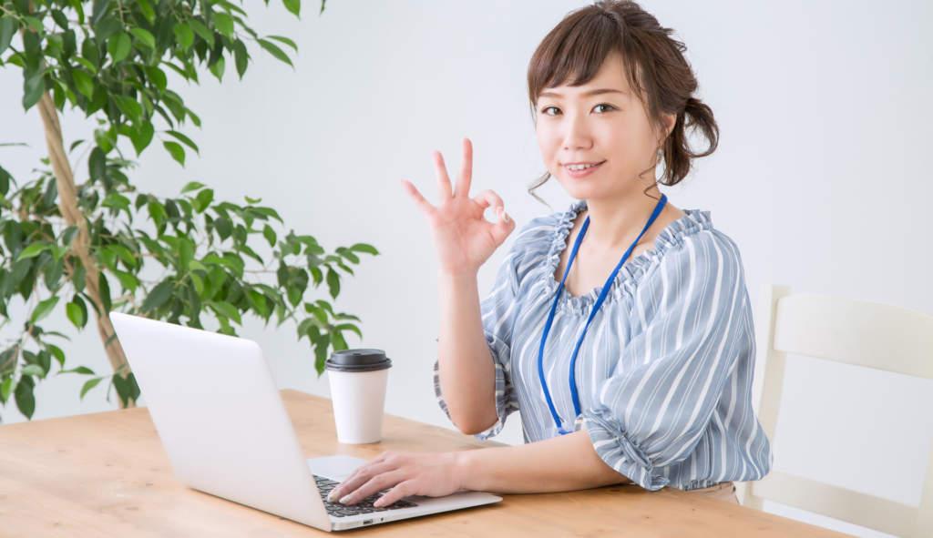 OKサインをしてパソコンを扱う女性
