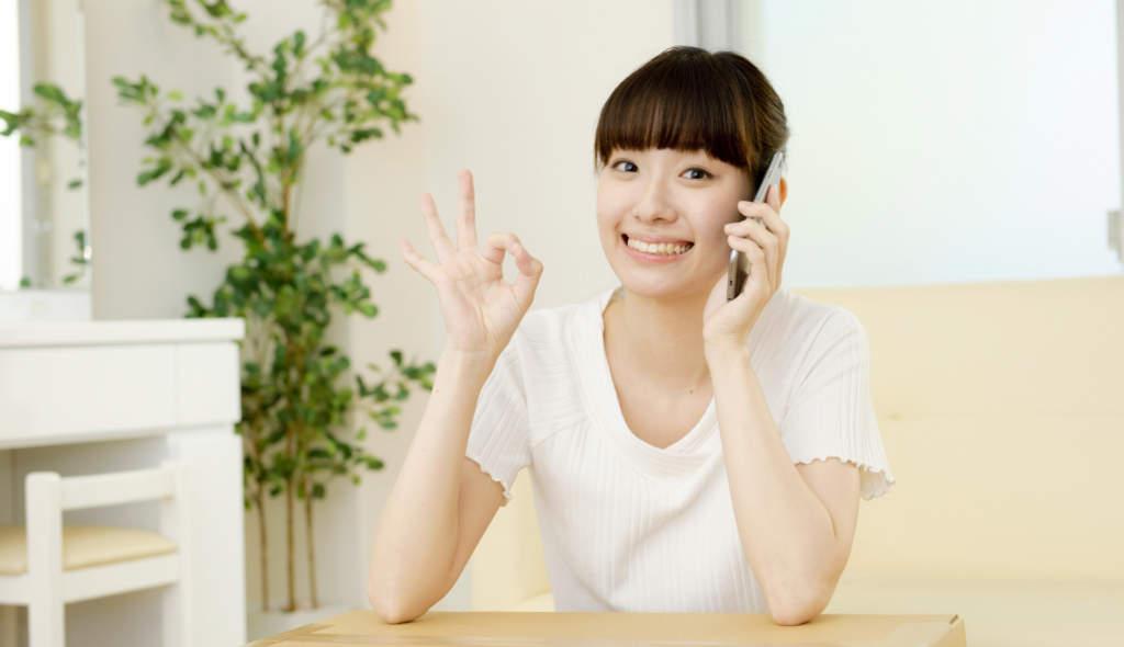 電話をしながらOKサインをする女性