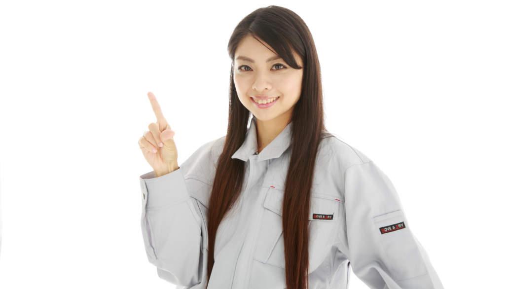 指を指す作業服の女性