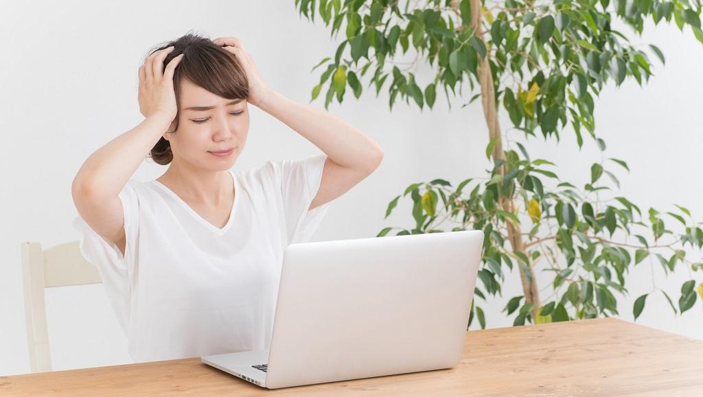 ノートパソコンを見て頭を抱える女性